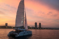 Sailing catamaran at the sunset in front of Olympic Port in Barcelona