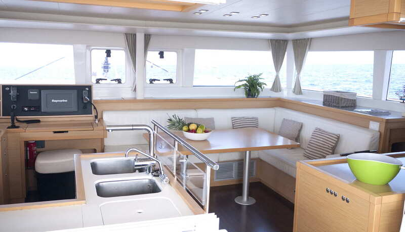 Interior view of the kitchen and the saloon of the catamaran Lagoon 450